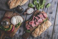 牛排三明治,切的烤牛肉 家庭焙制的面包,无盐干酪乳酪,菠菜 库存图片