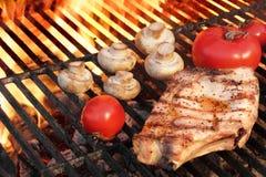 牛排和菜炭灰被烤在发火焰BBQ格栅 免版税库存图片