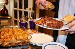 牛排和龙虾在板材举行了在一顿自助餐用拿着酿蘑菇的匙子手从盘-选择聚焦 免版税库存照片