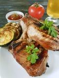 牛排油煎的部分番茄酱在木背景,可口啤酒烹调了 库存图片