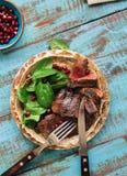 牛排烤与菠菜叶子和石榴在板材 免版税图库摄影