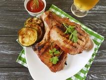 牛排热的油煎的部分番茄酱在木背景,可口啤酒烹调了 库存图片