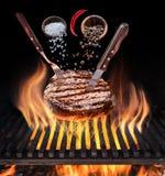 牛排烹调 概念性占领夫妇藏品光照片次幂表示 牛排用香料和利器在燃烧的格栅花格下 免版税库存照片