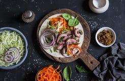 牛排玉米粉薄烙饼用烂醉如泥的红萝卜和圆白菜在一个木切板在黑暗的背景 免版税库存图片