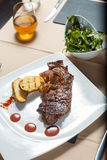 牛排用与沙拉边的烤土豆 免版税库存图片