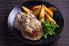 牛排用蘑菇奶油沙司、土豆楔子和绿豆 库存照片