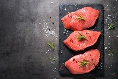 牛排用迷迭香和香料在黑背景 免版税库存图片