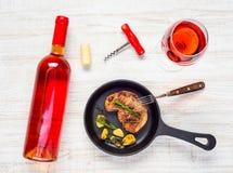 牛排用玻璃和瓶玫瑰酒红色 免版税图库摄影