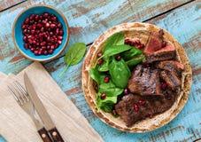 牛排的关闭烤与菠菜叶子和石榴 免版税图库摄影