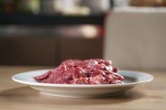 牛排的未加工的新鲜的切的牛肉在厨房用桌上的板材 库存照片