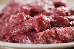 牛排的未加工的新鲜的切的牛肉在厨房用桌上的板材 库存图片