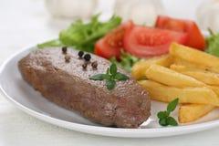 牛排肉餐用油炸物、菜和莴苣在板材 免版税库存照片