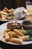 牛排饼、芯片、豌豆和小汤在一块板材在一张木客栈桌上 库存照片