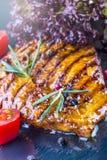 牛排鸡胸脯橄榄油西红柿以子弹密击和迷迭香草本 库存照片