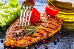 牛排鸡胸脯橄榄油西红柿以子弹密击和迷迭香草本 免版税库存图片