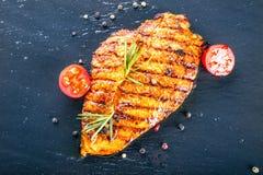 牛排鸡胸脯橄榄油西红柿以子弹密击和迷迭香草本 免版税库存照片