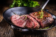 牛排 在平底锅的水多的中等肋骨眼睛牛排切片在木板用叉子和刀子草本香料和盐 免版税图库摄影