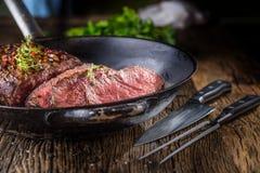 牛排 在平底锅的水多的中等肋骨眼睛牛排切片在木板用叉子和刀子草本香料和盐 免版税库存图片