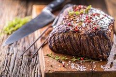 牛排 在平底锅的水多的肋骨眼睛牛排在木板用草本和胡椒 免版税库存照片