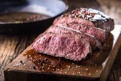 牛排 在木板的水多的中等肋骨眼睛牛排切片用叉子和刀子草本香料和盐 免版税库存图片