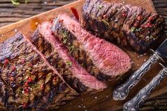 牛排 在木板的水多的中等肋骨眼睛牛排切片用叉子和刀子草本香料和盐 免版税图库摄影