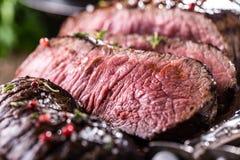 牛排 在木板的水多的中等肋骨眼睛牛排切片用叉子和刀子草本香料和盐 免版税库存照片