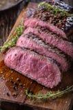 牛排 在木板的水多的中等肋骨眼睛牛排切片用叉子和刀子草本香料和盐 库存图片