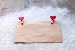 牛皮纸信封与两红色晒衣夹的以心脏的形式,华伦泰` s天,人` s态度 免版税库存图片