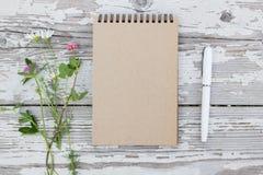 牛皮纸螺纹笔记本、白色笔和夏天花在土气木背景 大模型 免版税图库摄影