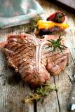 牛肉在黑暗的老木板的丁骨牛排 免版税库存照片