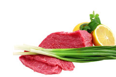 牛肉块与柠檬片式和葱的牛排。 库存图片