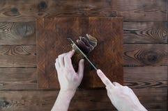 牛肉干切口的部分到在一张切口桌上的切片里与在葡萄酒木背景的一把厨刀 图库摄影
