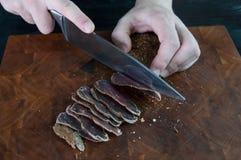 牛肉干切口的部分到在一张切口桌上的切片里与在葡萄酒木背景的一把厨刀 库存照片