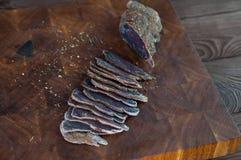 牛肉干切口的部分到在一张切口桌上的切片里与在葡萄酒木背景的一把厨刀 库存图片