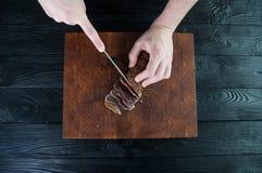 牛肉干切口的部分到在一张切口桌上的切片里与在葡萄酒木背景的一把厨刀 免版税库存照片