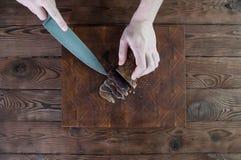 牛肉干切口的部分到在一张切口桌上的切片里与在葡萄酒木背景的一把厨刀 免版税图库摄影