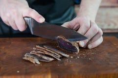 牛肉干切口的部分到在一张切口桌上的切片里与在葡萄酒木背景的一把厨刀 免版税库存图片