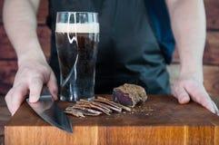 牛肉干切口的部分到在一张切口桌上的切片里与黑啤酒玻璃和一把厨刀在葡萄酒木背景 免版税库存图片