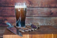 牛肉干切口的部分到在一张切口桌上的切片里与黑啤酒玻璃和一把厨刀在葡萄酒木背景 库存图片