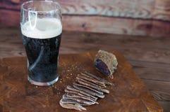 牛肉干切口的部分到在一张切口桌上的切片里与黑啤酒玻璃和一把厨刀在葡萄酒木背景 库存照片