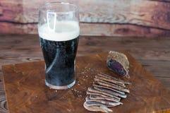 牛肉干切口的部分到在一张切口桌上的切片里与黑啤酒玻璃和一把厨刀在葡萄酒木背景 免版税库存照片