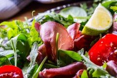 牛肉干bresaola 沙拉bresaola芝麻菜婴孩菠菜蕃茄石灰和乳酪巴马干酪 库存照片