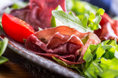 牛肉干bresaola 沙拉bresaola芝麻菜婴孩菠菜蕃茄石灰和乳酪巴马干酪 免版税库存图片