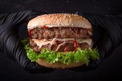 牛肉汉堡 在黑手套的手拿着一个可口,水多,新鲜的双重汉堡包 特写镜头 安置文本 免版税库存图片