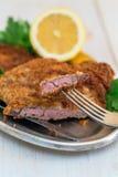 牛肉炸肉排片断在叉子、柠檬和荷兰芹的 库存图片