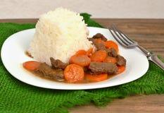 从牛肉肉和红萝卜的捷克膳食用在白色板材的米在黑暗的木背景的绿色粗麻布布料 图库摄影