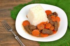 从牛肉肉和红萝卜的捷克膳食用在白色板材的米在黑暗的木背景的绿色粗麻布布料 免版税库存照片