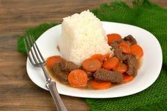 从牛肉肉和红萝卜的捷克膳食用在白色板材的米在黑暗的木背景的绿色粗麻布cloteh 免版税库存照片