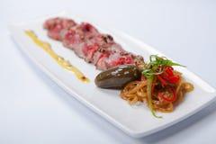 牛肉carpaccio用调味汁和菜 免版税图库摄影