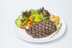 牛腰肉排服务用新鲜的油煎的沙拉和法语 免版税库存图片
